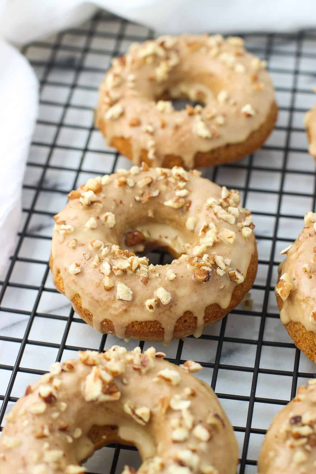 Pumpkin pecan donuts are warmly spiced and baked for a cake-y, pumpkin bread-like donut. They're covered in a maple vanilla glaze and more chopped pecans for a fall touch!