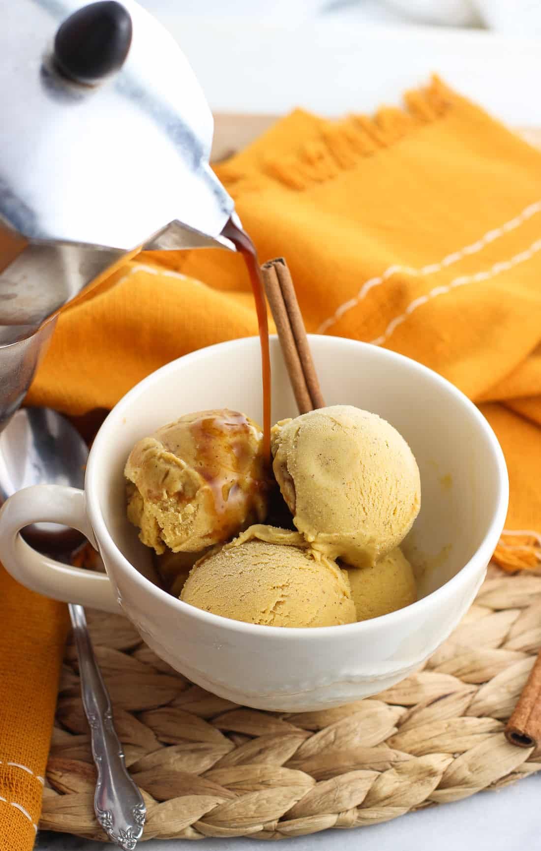 Four small scoops of pumpkin gelato in a large mug with espresso being poured over top, all garnished with a whole cinnamon stick