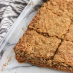 Oatmeal maple bars with a pecan graham crust are chewy like oatmeal cookies and warmly spiced with cinnamon and maple extract. Enjoy old-fashioned oats in dessert form with these bars!