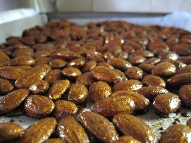 Gingerbread roasted almonds on a sheet pan.