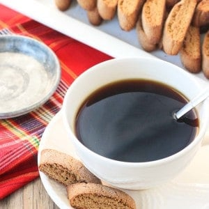Two biscotti accompanying a cup of coffee next to the full tray of cookies.