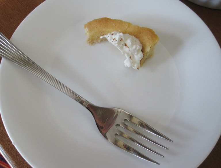 Just the crust remaining of a slice of pie on a plate with a fork.