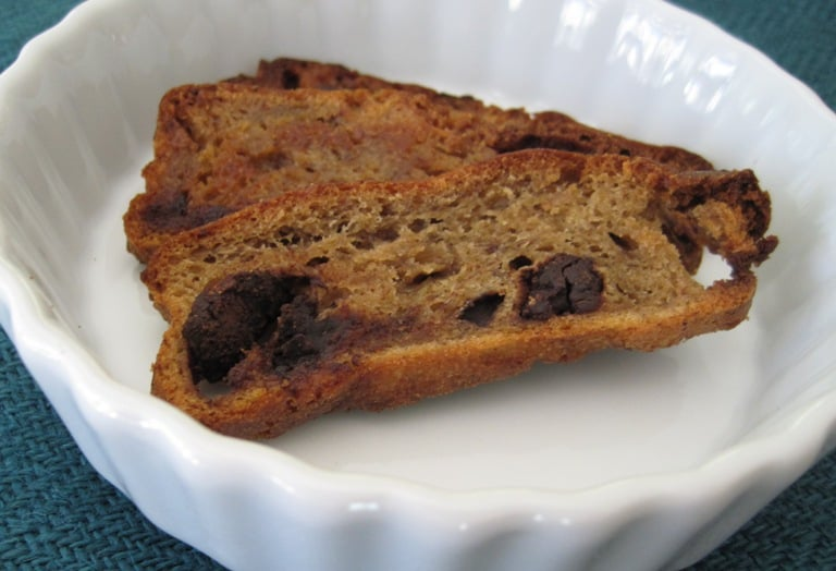 A toasted banana bread chip in a small ceramic bowl.