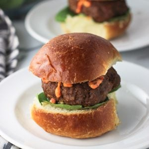 A turkey burger slider, with lettuce and chili garlic sauce, on a small slider bun on a plate with another in the background