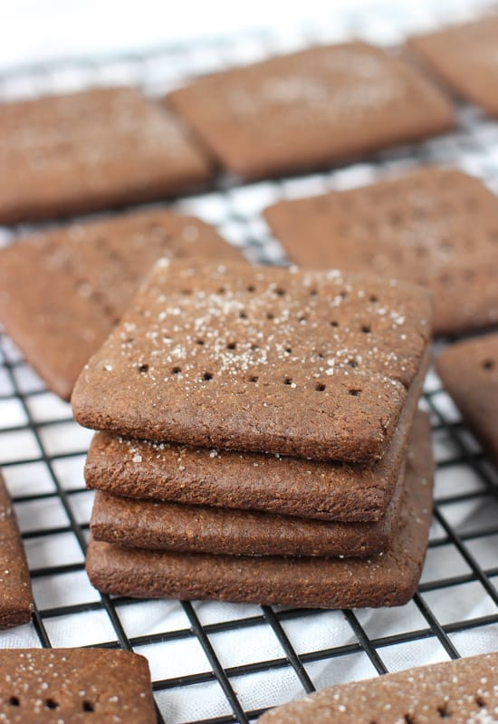 A stack of four graham crackers on a cooling rack surrounded by other crackes