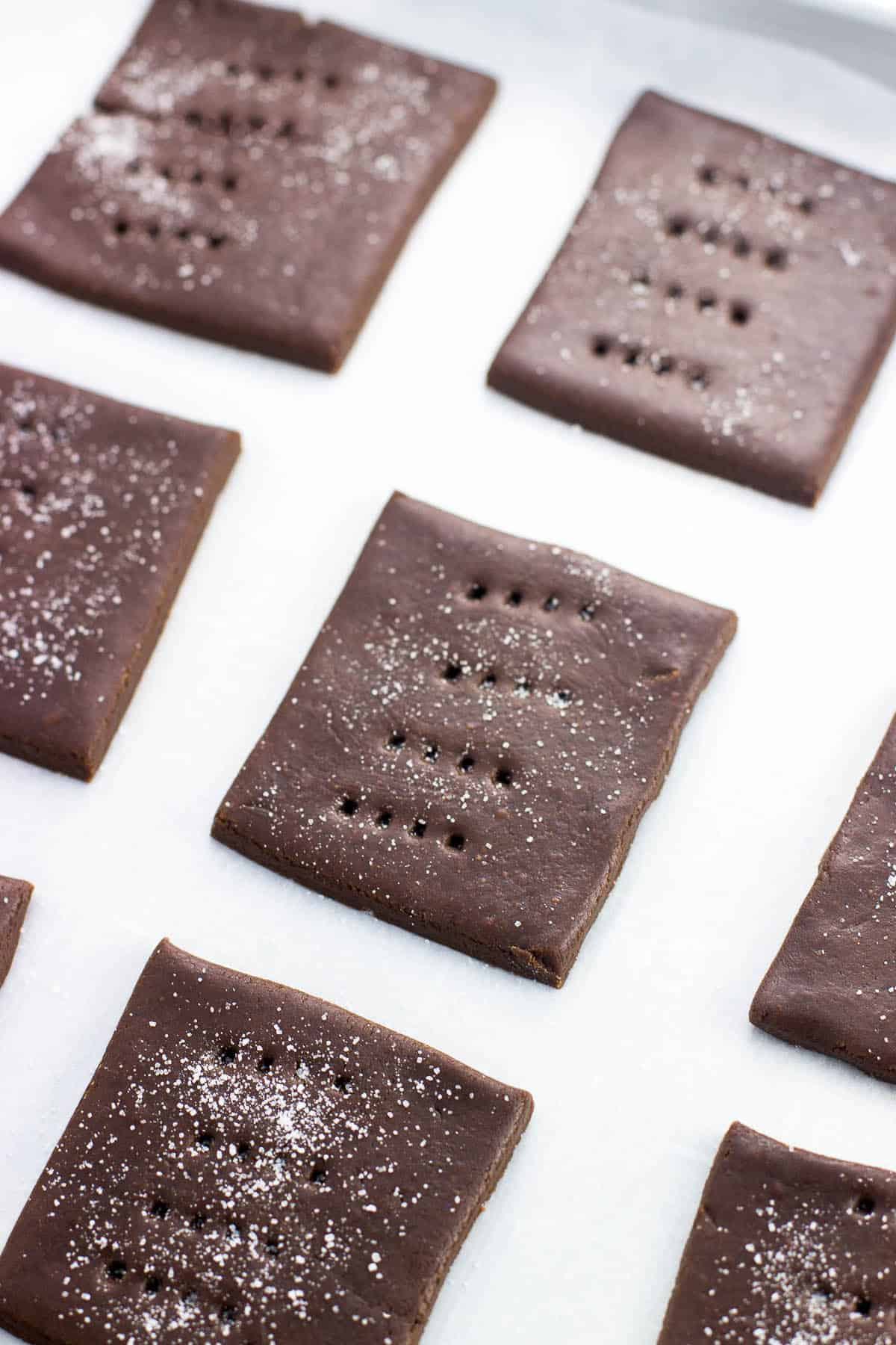 Squares of chocolate graham dough dusted with sugar on a parchment-lined baking sheet before going in the oven