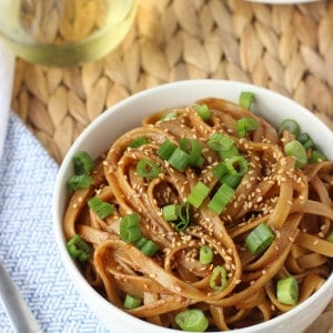 A bowl of almond butter noodles garnished with sliced green onion and sesame seeds.