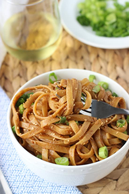 A fork twirled around almond butter noodles in a bowl.