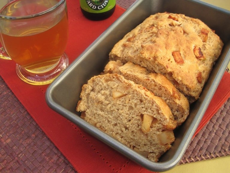 A loaf of half-sliced cider bread in a tin next to a glass of cider.