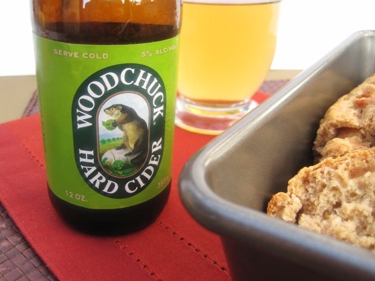 A close-up of a bottle of hard cider next to the loaf of bread.