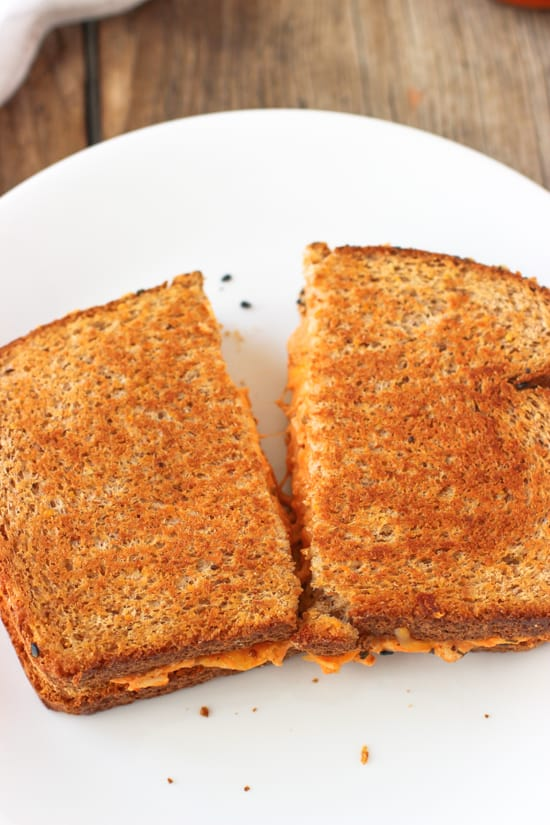 Two halves of the grilled cheese being pulled apart from one another on a plate.