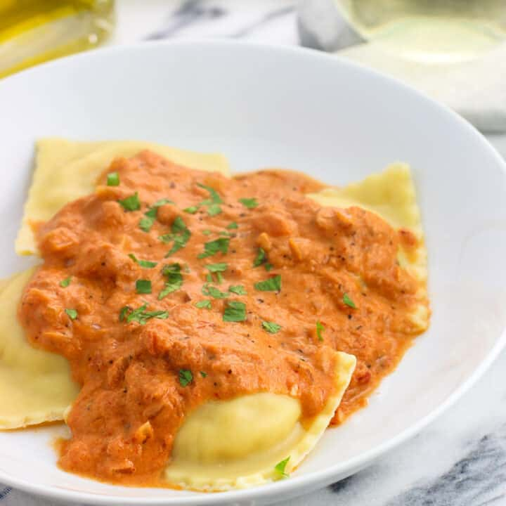 A dinner plate of ravioli and vodka sauce garnished with fresh basil.