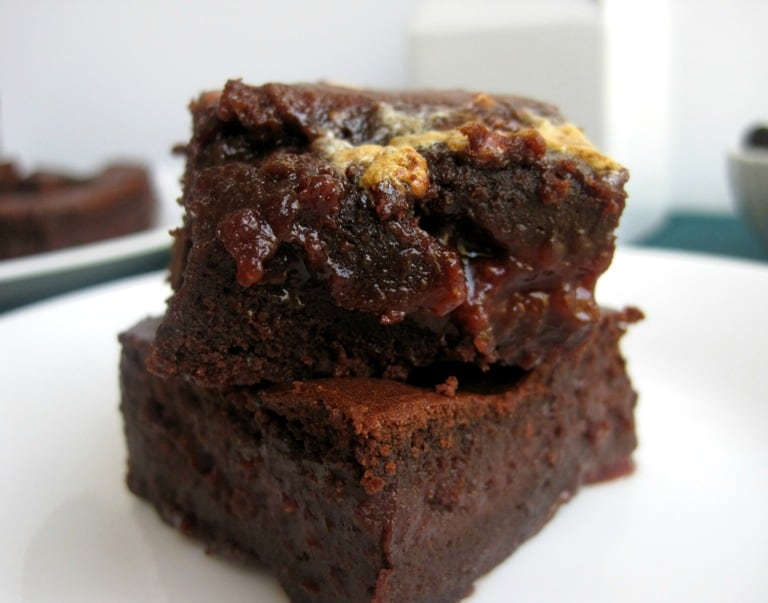 A stack of two brownies on a plate.