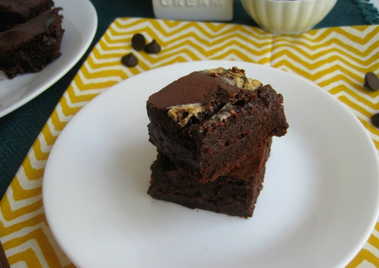 Two brownies stacked on a plate.