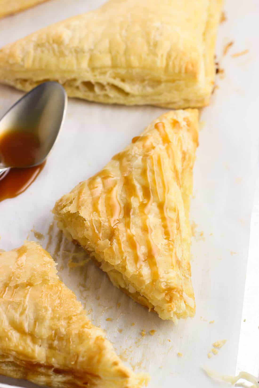 A flaky turnover cut in half and drizzled with caramel sauce