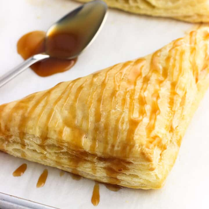 Coconut pineapple turnovers are made SO easy with puff pastry. Just three ingredients form these simple pastries that are complemented beautifully with a drizzle of homemade salted caramel sauce.