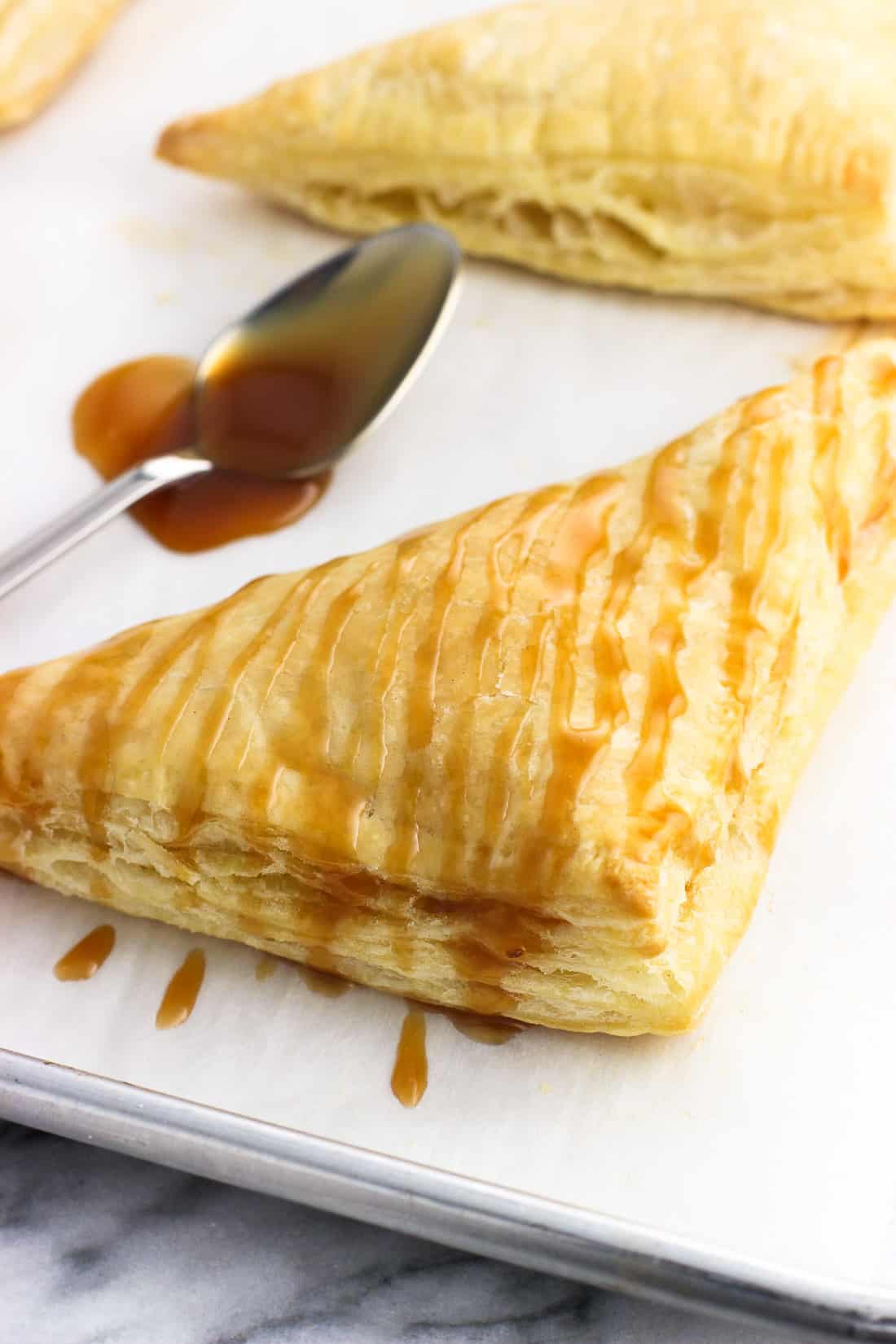 A caramel-drizzled turnover on a baking sheet.