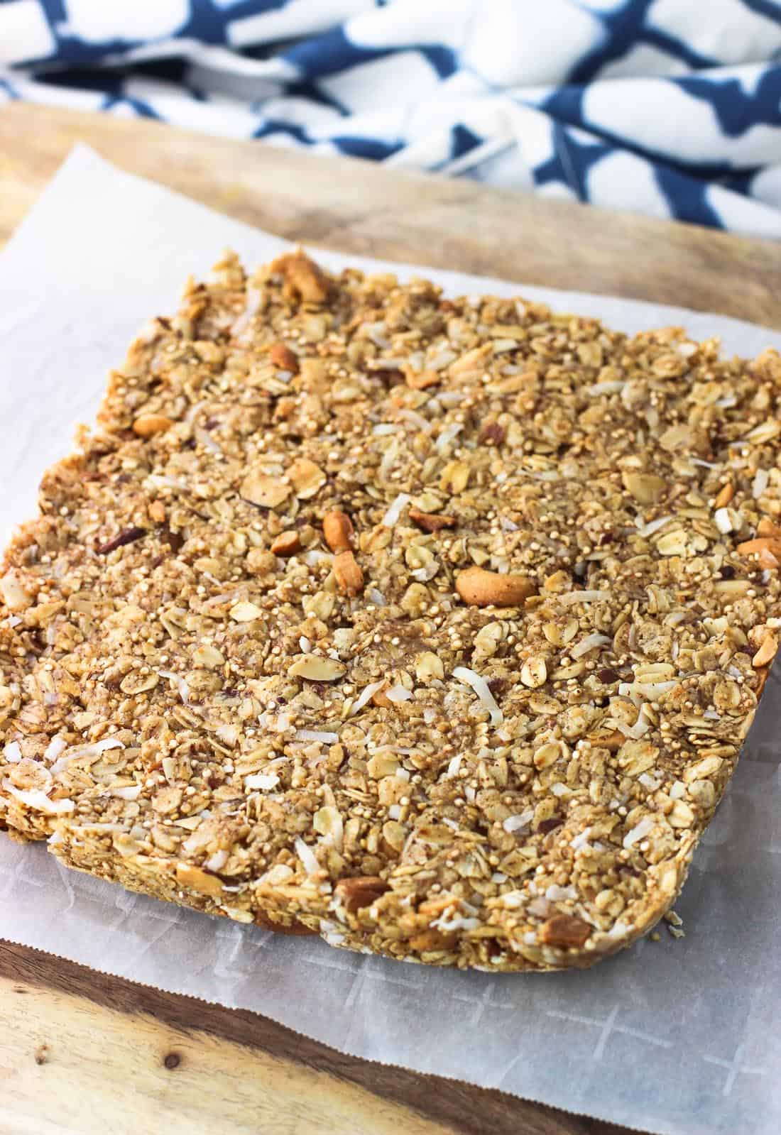 The square granola bar mixture on a parchment-lined cutting board before being cut into slices