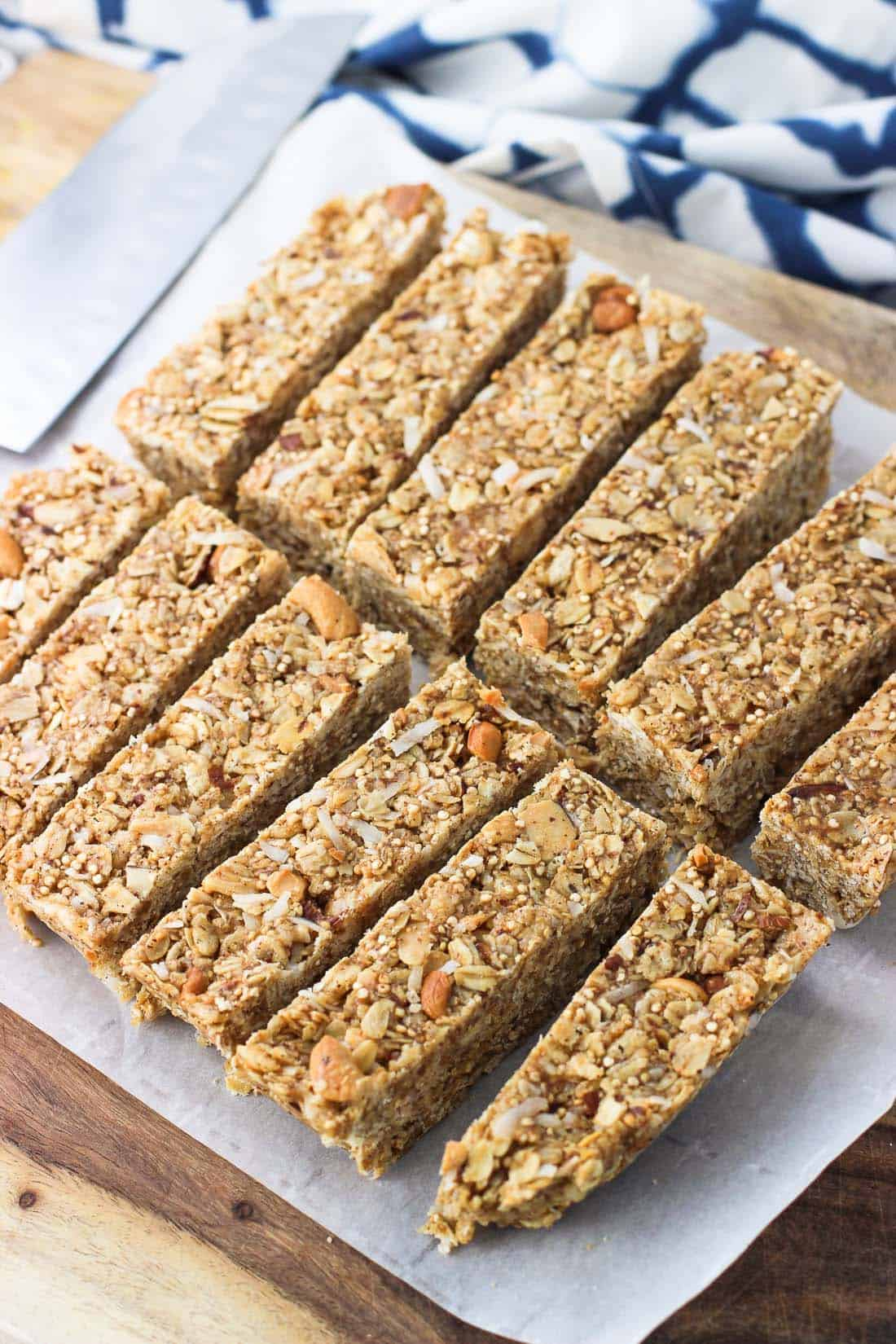 Twelve granola bars just after being sliced on the cutting board