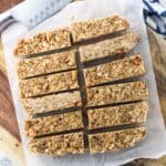 Twelve granola bars sliced on a sheet of parchment paper on a wooden board