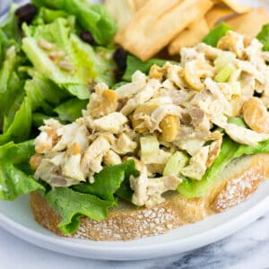 An open-face chicken salad sandwich next to a side salad and pita chips.