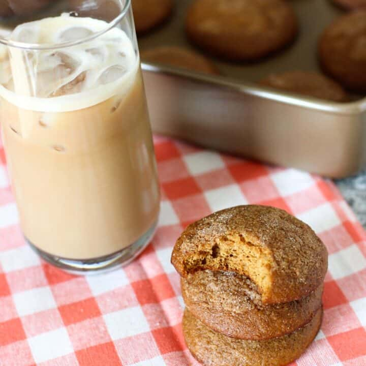 A stack of muffin tops next to an iced latte in a glass and the tray of muffin tops.