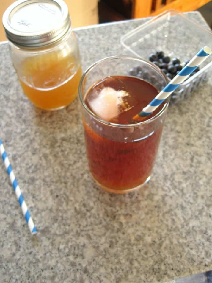 A glass of iced tea on a counter with a jar of simple syrup.