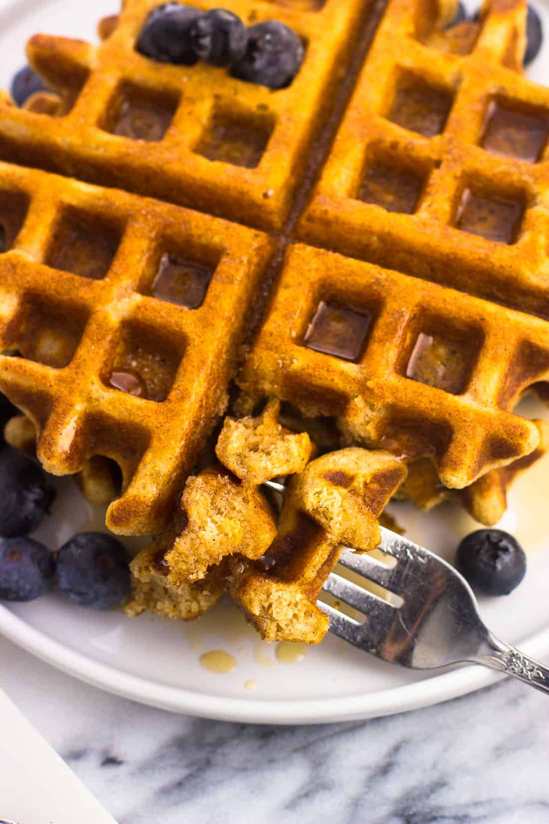 A forkful of waffle on a plate with maple syrup and blueberries