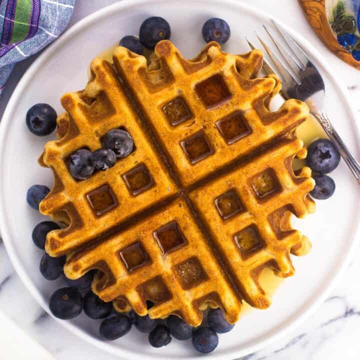 Whole wheat waffles on a plate served with a maple syrup drizzle and fresh blueberries