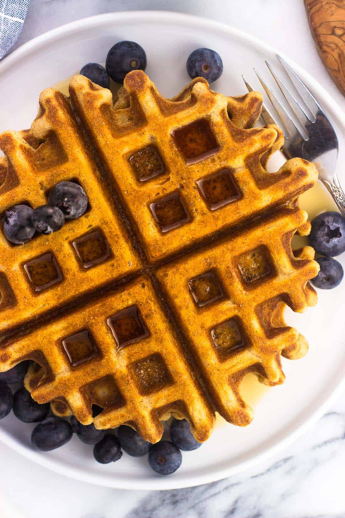 An overhead shot of whole wheat waffles with maple syrup and fresh blueberries