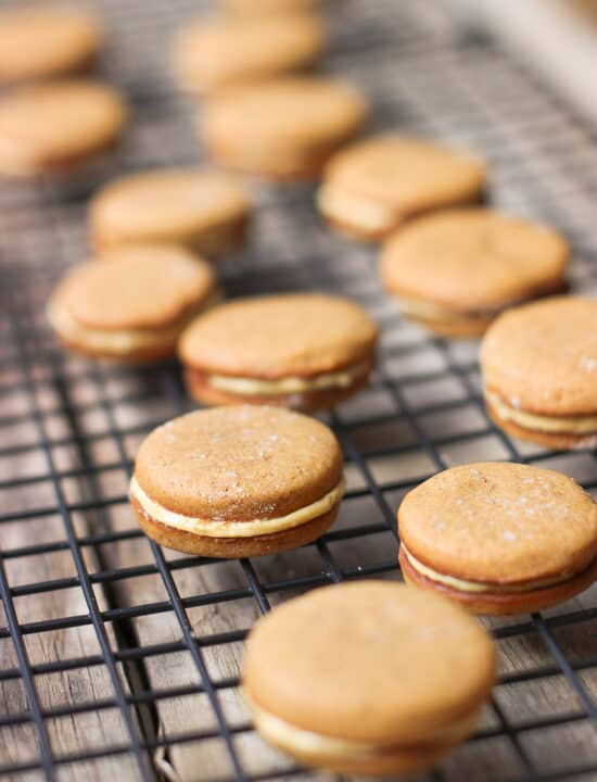 Pumpkin sandwich cookies assembled on a wire rack.