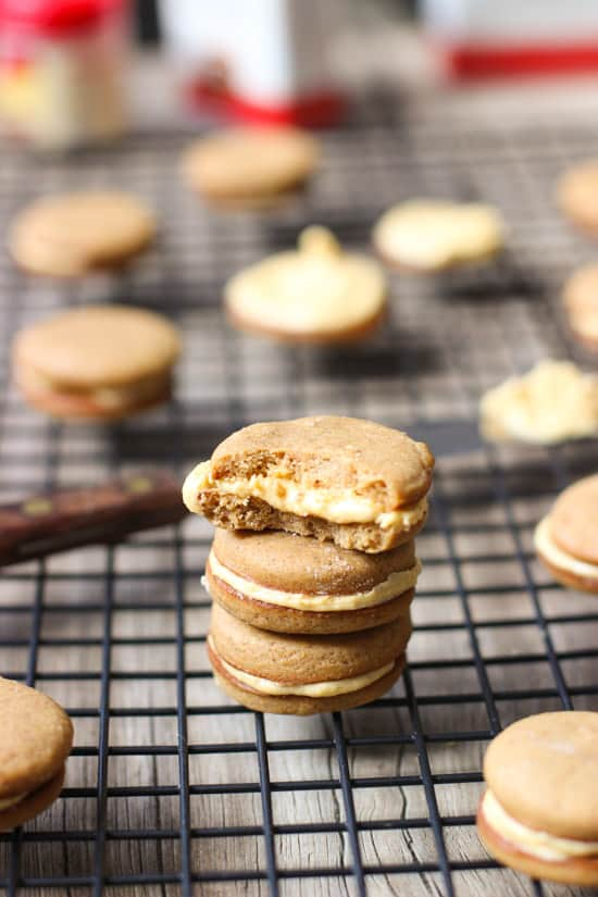 A stack of pumpkin sandwich cookies on a wire rack with a bite taken out of the top one.