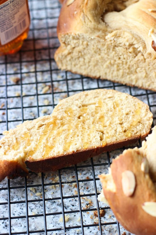 A close-up of a slice of bread on a wire rack drizzled with honey