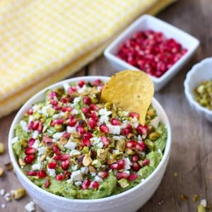 A tortilla chip in a bowl of guacamole next to little bowls of pomegranate arils and pistachios.