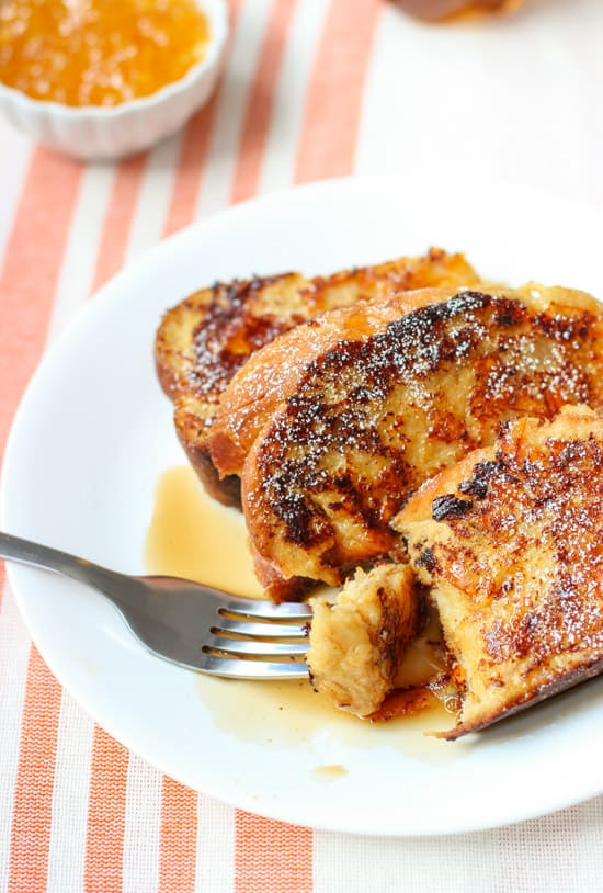 Three slices of french toast on a plate drizzled with maple syrup.