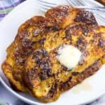 Two slices of challah french toast on a plate with maple syrup, a pat of butter, and forks.