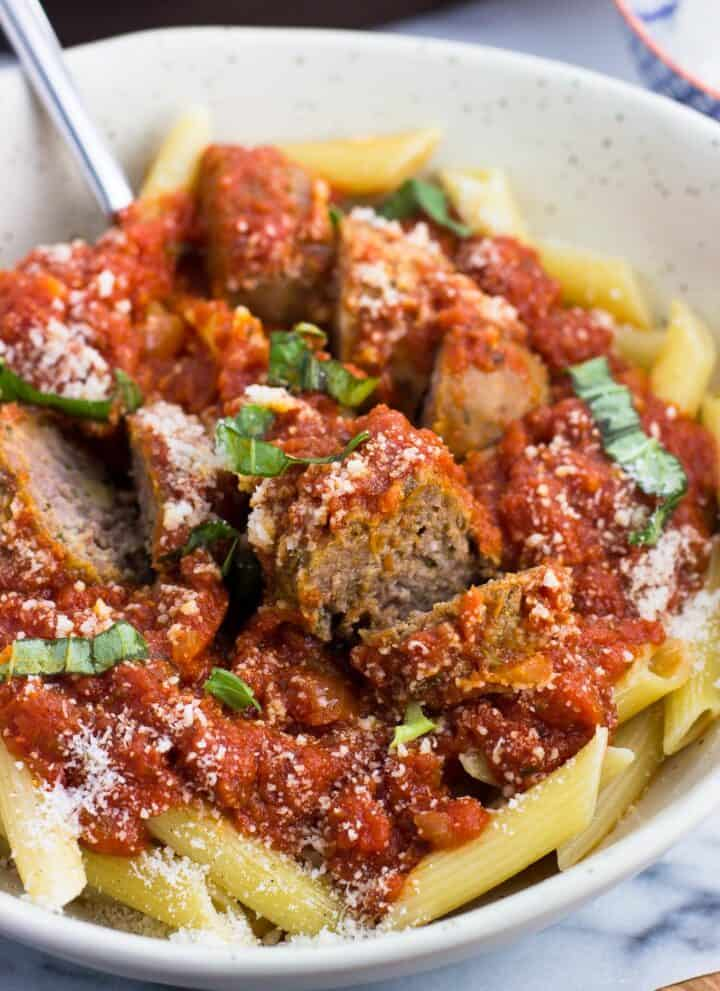 A bowl of Sunday sauce with meatballs and sausage served over penne pasta and garnished with Parmesan