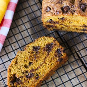 A slice of pumpkin banana bread on a wire rack next to the rest of the loaf.