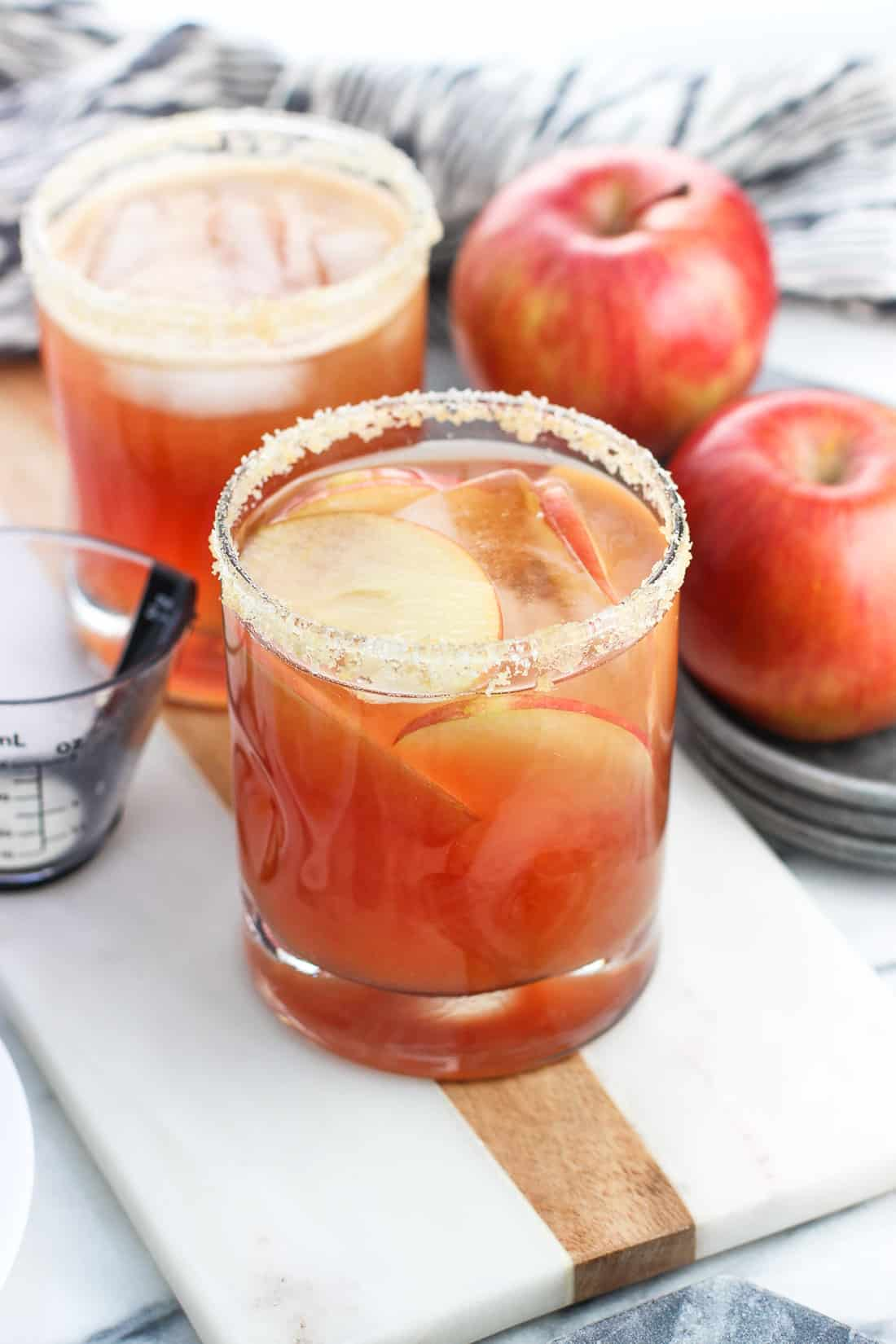 This easy cranberry apple margarita recipe is a crowd pleaser! Cranberry juice and apple cider join tequila and a splash of orange juice for a tart, extra fruity spin on a cocktail classic with a golden sugar rim.
