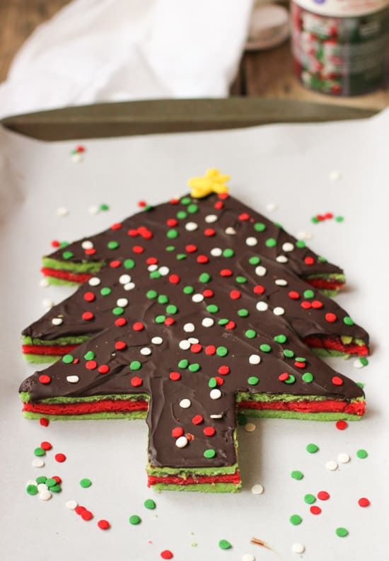 A Christmas tree-shaped rainbow cookie cake on a parchment-lined baking sheet.
