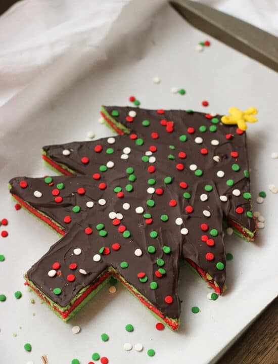 A Christmas tree-shaped and decorated slab of rainbow cookies on a parchment-lined baking sheet.