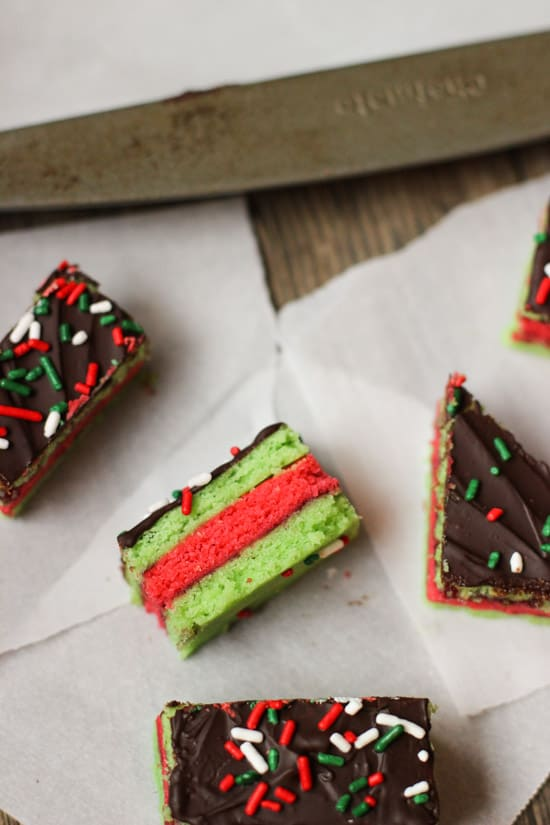 Various shaped Christmas rainbow cookies on sheets of parchment paper.