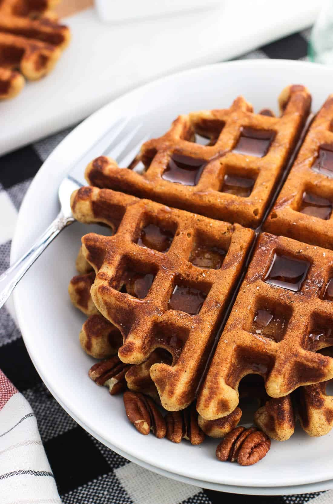 Two waffles on a plate served with maple syrup and pecans