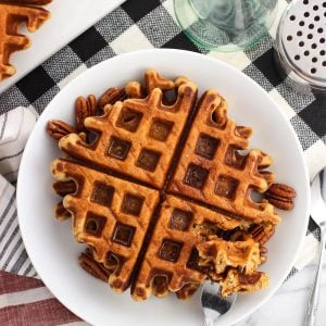 An overhead shot of waffles on a plate served with maple syrup and pecans