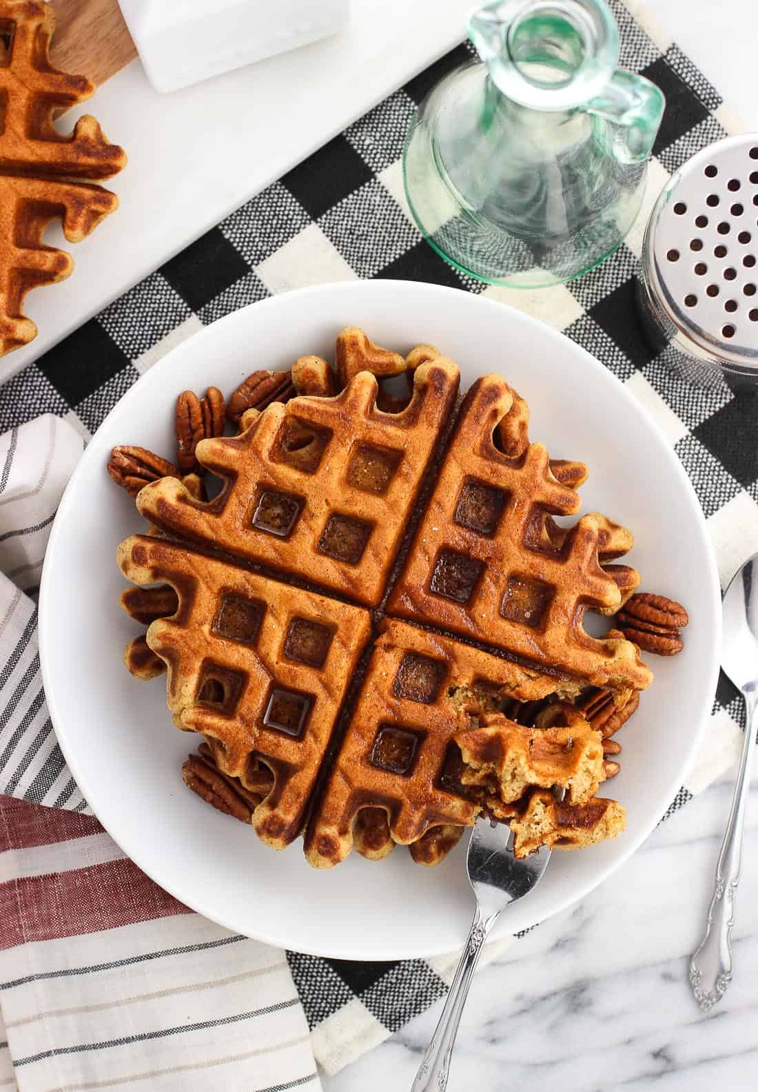 An overhead shot of two gingerbread waffles served on a plate with maple syrup and pecans