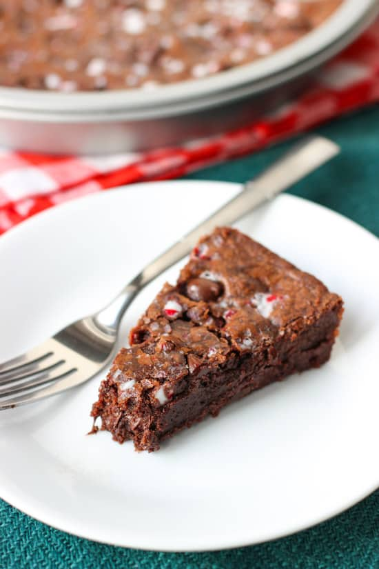 A slice of cookie cake on a plate with a fork and one bite removed.