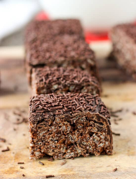 Lined up chocolate rice krispie treats on a wooden cutting board.