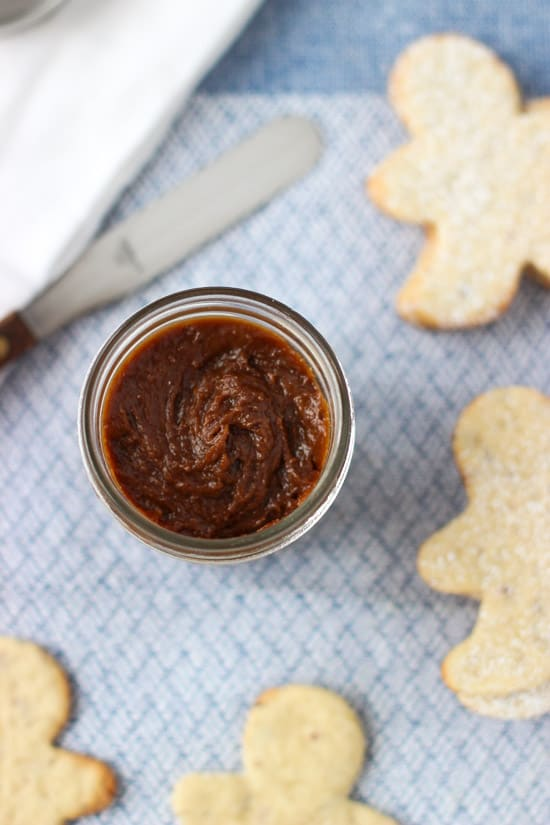 A jar of gingersnap cookie butter next to person-shaped sugar cookies.