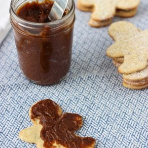 Gingersnap cookie butter spread onto a cookie in front of the jar with a knife in it.