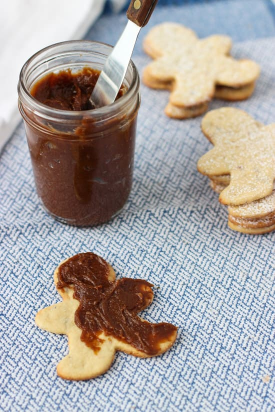 An offset spatula in a jar of cookie butter after spreading some on a cookie.